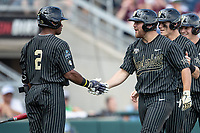 Vanderbilt Commodores outfielder Stephen Scott (19) is greeted by teammate Harrison Ray (2) after his second home run of Game 8 of the NCAA College World Series against the Mississippi State Bulldogs on June 19, 2019 at TD Ameritrade Park in Omaha, Nebraska. Vanderbilt defeated Mississippi State 6-3. (Andrew Woolley/Four Seam Images)