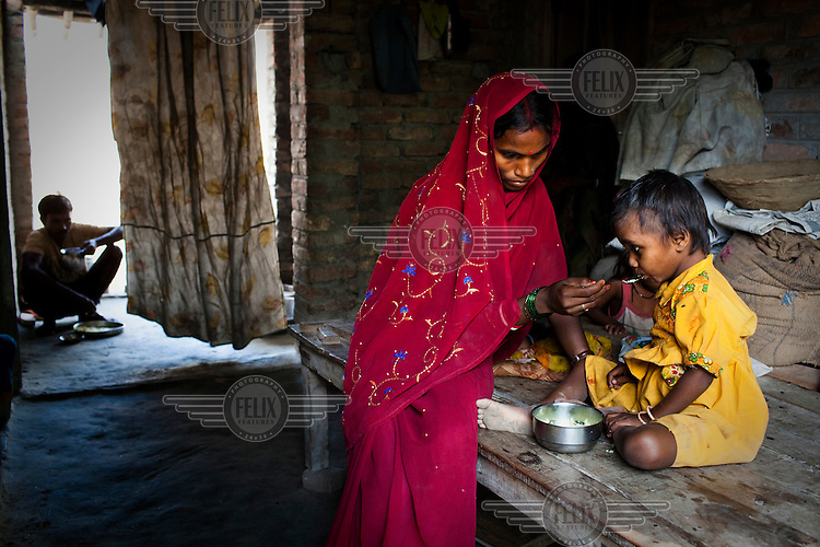 Reeta Devi feeds her four year old daughter Rimjhim in their house in Bishambharpur village in the Muzaffarpur district of Bihar. Reeta Devi took advantage of the government scheme of institutional delivery and was compensated for the delivery. Since 2008 the Legatum Foundation and Geneva Global have been investing in the training of medical staff to improve the lives of people living in 600+ villages in the region. The NGOs are delivering cost effective interventions to address treatment, care and prevention of diseases, disability and preventable deaths amongst infants, adolescent girls and women of child-bearing age. There is statistical and anecdotal evidence that there have been vast improvements and a total of 40-50% increased immunization for all children under 6 has meant that communities can be serviced and educated long term.