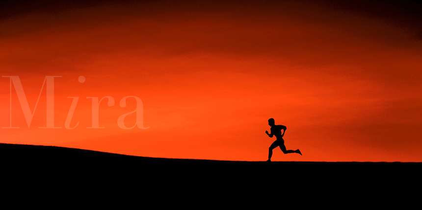 The silhouette of a man running up a slight incline; high contrast of land, figure and crimson sky.