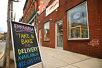 """The outside of Mi Empanada advertising their """"Take & Bake"""" pickup and delivery services is shown on Butler Street on Friday March 20, 2020 in the Lawrenceville neighborhood of Pittsburgh, Pennsylvania. (Photo by Jared Wickerham/Pittsburgh City Paper)"""