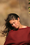 A Native American Indian women with black hair flying in the wind in fall