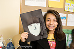 Education Middle School grade 8 art activity cut paper self portraits girl holding up art work and posing horizontal