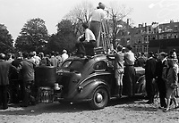 A film camera crew records a demonstration from the roof of a passenger car in The Hague. The car is still running on a wood gas generator.