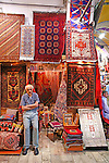 A vendor stands in front of his stall at the Grand Bizarre, displaying many Turkish rugs and other weavings.