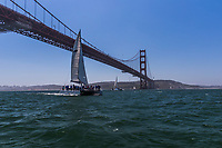 A catamaran loaded with sightseers sails under the Golden Gate Bridge passing from San Francisco Bay into the Pacific Ocean.  On average, 120,000 vehicles cross the Golden Gate bridge every day.  Traffic under the bridge is lighter.