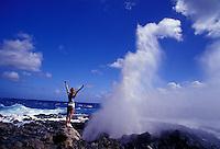 Woman watching Holona blowhole erupt, Kaiwi coastline on Oahu, Hawaii