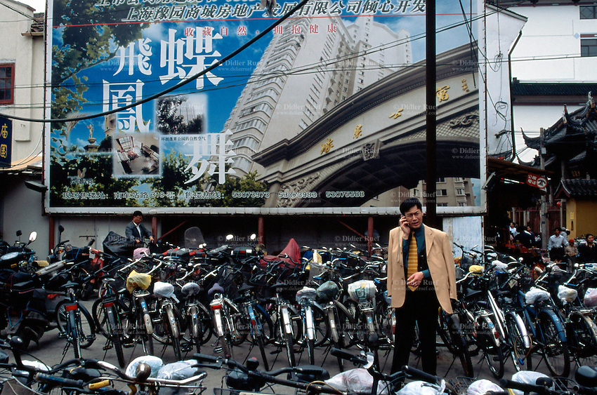 China. Shanghai. Downtown. City center. Businessman with tie and jacket using a mobile phone. On the poster, new condominiums for promotional sale. © 2002 Didier Ruef