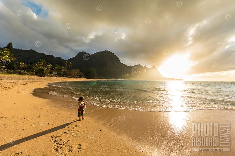 A girl plays near the sandbar at sunset at Tunnels Beach, Ha'ena, Kaua'i.