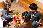 Education preschool 3-4 year olds group of two girls and a boy playing with toy plastic hammers and construction toy horizontal