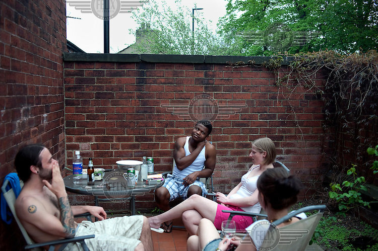 Antonio Bravo relaxes with his housemates in the garden of their home in Leeds.