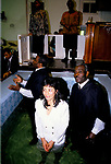 Church of God of Prophecy  In the church hall at Tubbs Road london the pastor and his assistant baptise a young woman. As in most 'born again' churches candidates make their own decision to be baptised by full immersion in the name of the Father , Son and Holy Ghost.