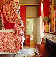 The guest bedroom is dominated by a lit a la polonaise with pretty red and white floral bed hangings