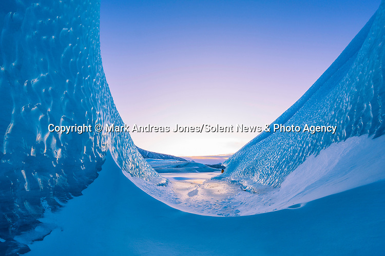 "Pictured: A hiker is dwarfed by the opening of a huge ice cave.   The ice cave in Iceland formed inside of an iceberg which was locked into a frozen lagoon as temperatures dropped to -12 degrees Celsius.<br /> <br /> Professional photographer Mark Andreas Jones captured these shots looking out of two caves in Hoffellsjökull as his friend Oskar Arason walked by.   Mr Jones, 49, from Gosport, Hants, said: ""Up to 90 per cent of the iceberg was submerged so it was impossible to gauge the full size of it, but the smallest of the two caves was easily the size of a four-bedroom house above the water level.   SEE OUR COPY FOR DETAILS<br /> <br /> Please byline: Mark Andreas Jones/Solent News<br /> <br /> © Mark Andreas Jones/Solent News & Photo Agency<br /> UK +44 (0) 2380 458800"