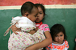 A Naua Indian girl cradles her little brother in the village of Ayotzinapan, Puebla. Photo by Heriberto Rodriguez/ CGEIB