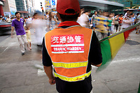 CHINA. A traffic warden sports a bi-lingual vest in central Beijing. The rise in use of English in China is evident on the streets of Beijing where store-fronts, billboards and clothes all sport English words and phrases. 2009
