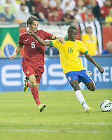 Brazil midfielder Ramires (16) kicks a pass as Portugal defender Fabio Coentrao (5) attempts to tackle.  In an International friendly match Brazil defeated Portugal, 3-1, at Gillette Stadium on Sep 10, 2013.