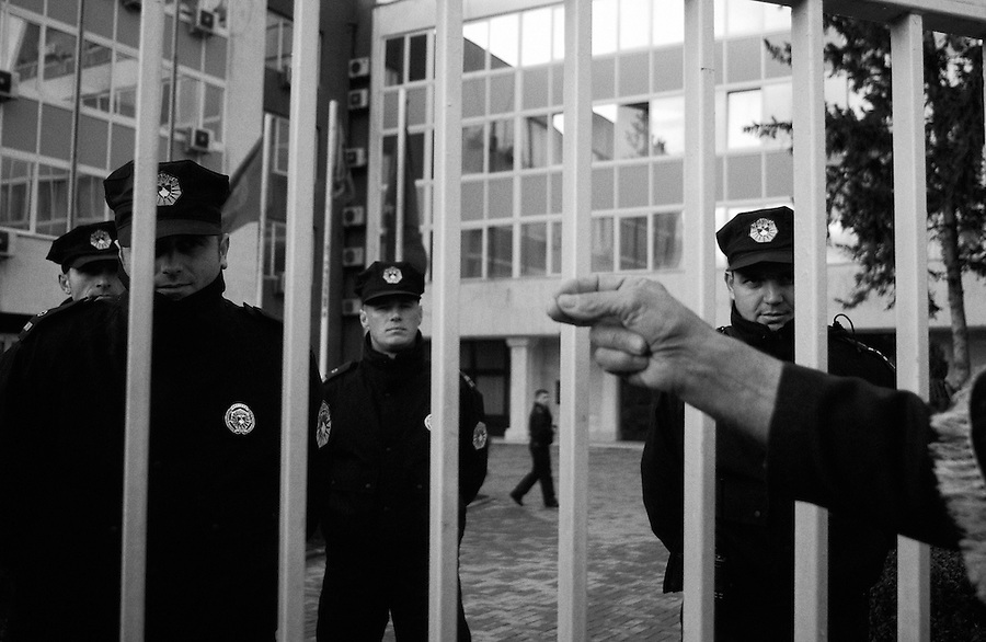 Man facing off with Kosovar Police behind fence in Pristina, Kosovo.