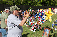 A visitor snaps a picture of wreaths while others reflect while viewing names on the Vietnam Veterans Memorial in Washington, DC.