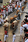 Participants run in front of Alcurrucen's bulls during the first bull run of the San Fermin Festival, on July 7, 2013, in Pamplona, northern Spain. The festival is a symbol of Spanish culture that attracts thousands of tourists to watch the bull runs despite heavy condemnation from animal rights groups. (c) PEDRO ARMESTRE
