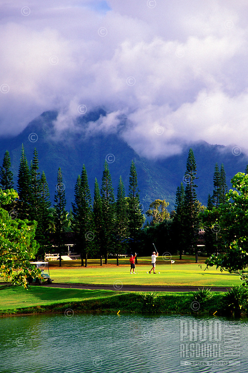 A golfer tees off at a beautiful Princeville, Kauai golf course with tall pine trees and cloud covered mountains in the background.
