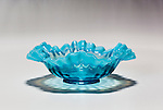 Looking into a clear blue candy bowl,oblique angle from above, reflection and shadow on white gradiated background.