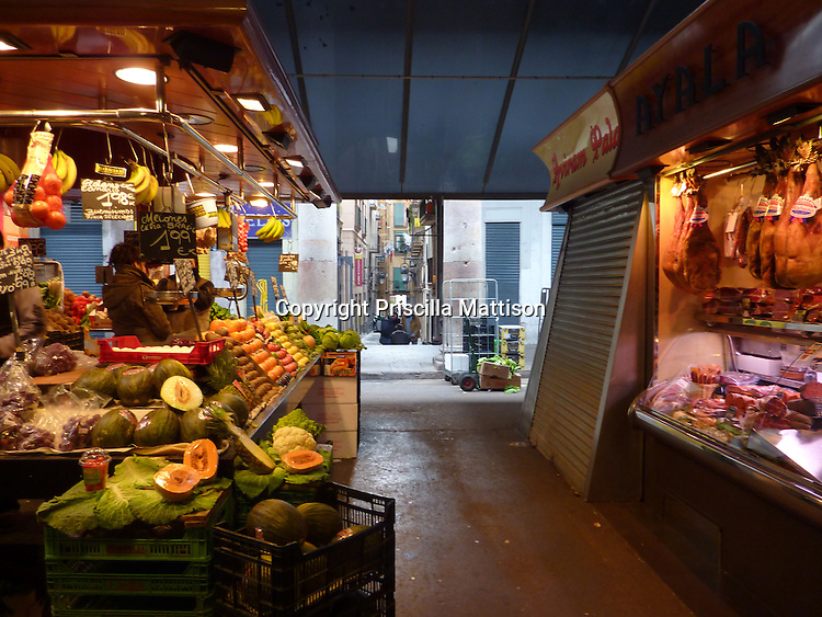 Barcelona, Spain - January 31, 2011:  Brightly-lit stalls in a food market are open to an alley.