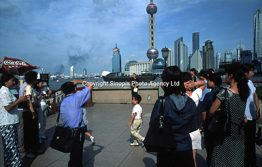 Tourists take photos with Pudong's towers in the background..04-JUL-01