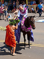 Hula dancer passing a ho'okupu gift to a Pa'u rider on horseback in King Kamehameha Day Parade, North Kohala, Big Island of Hawaii, Kapa'au Town.