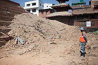 Nepali police man stands in front of the rubble of a destroyed temple at Kathmandu Durbar Square, Kathmandu, Nepal. May 03, 2015