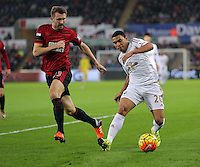 Jefferson Montero of Swansea (R) crosses the ball, marked by Gareth McAuley of West Bromwich Albion during the Barclays Premier League match between Swansea City and West Bromwich Albion played at the Liberty Stadium, Swansea on December 26 2015