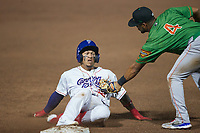 Jose Rodriguez (12) of the Kannapolis Cannon Ballers slides into third base ahead of the tag by Cristian Inoa (4) of the Down East Wood Ducks at Atrium Health Ballpark on May 5, 2021 in Kannapolis, North Carolina. (Brian Westerholt/Four Seam Images)
