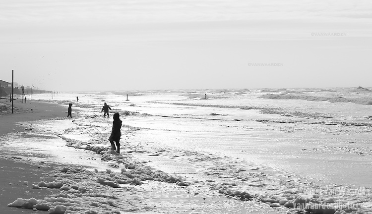 Playing in the sea foam on the Netherlands beach near Zandvoort aan Zee.
