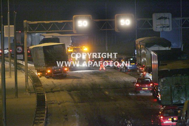 Arnhem, 261105<br /> Lange files in door invallende winter. Rond middernacht staan nog vele automobilisten in de file op gladde wegen. Zo ook op de A50 bij Arnhem.  Een vrachtwagen is geslipt en gaat weggesleept worden.<br /> Foto: Sjef Prins - APA Foto