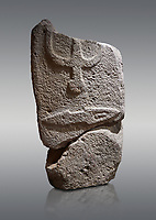 Central fragment of a Late European Neolithic prehistoric Menhir standing stone with carvings on its face side. The representation of a stylalised male figure would have started at the top with the remaons of  a carving of a falling figure with head at the bottom and 2 curved arms encircling a body above. at the bottom is a carving of a dagger running horizontally across the menhir.  Excavated from Piscina 'E Sali VI site,  Laconi. Menhir Museum, Museo della Statuaria Prehistorica in Sardegna, Museum of Prehoistoric Sardinian Statues, Palazzo Aymerich, Laconi, Sardinia, Italy. Grey background.