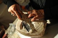 Artisti a San Lorenzo , quartiere storico di Roma. <br /> Jole Falco, scultrice nel suo studio mentre lavora la pietra saponaria.<br /> Artists in San Lorenzo, historic district of Rome. <br /> Jole Falco, sculptor in his studio while working saponaria stone.