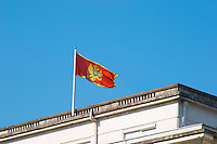 The Montenegrin flag flying on top of a building, red with a golden double headed eagle. Podgorica capital. Montenegro, Balkan, Europe.