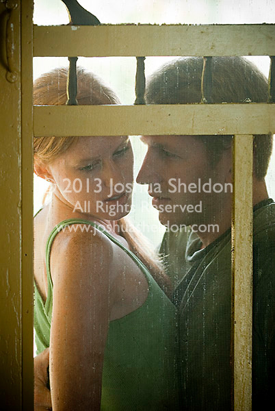 Young couple seated on porch viewed through screen door