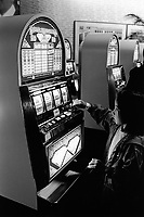 """Switzerland. Bern canton. Biel / Bienne , Expo 02. """" Money and value. The last taboo"""". A young girl plays with fake money on a Double Diamond slot machine. One-armed bandit. National exhibition. © 2002 Didier Ruef .."""