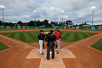 Batavia Muckdogs manager Tom Lawless (left) during the lineup exchange with Luke Montz (right) and umpires Cliburn Rondon, Ethan Gorsak, Joe Belangia, and Jon-Tyler Shaw before a NY-Penn League Semifinal Playoff game against the Lowell Spinners on September 4, 2019 at Dwyer Stadium in Batavia, New York.  Batavia defeated Lowell 4-1.  (Mike Janes/Four Seam Images)