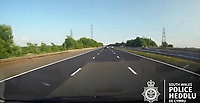 "Pictured: Dashcam video grab showing a blue Mini veering off after colliding with a silver Ford Mondeo on the M4 motorway near Port Talbot, Wales, UK in June 2018.<br /> Re: Two motorists have been convicted of dangerous driving following a road rage incident on the M4 near Port Talbot.<br /> Dash cam footage shows the two men repeatedly undertaking and tailgating each other along the eastbound carriageway in June last year.<br /> The incident eventually led to one of the vehicles – a blue Mini – flipping onto its roof with the driver fortunate to get out of the car unharmed.<br /> Paul Carpenter, aged 44, from Boxhill in Surrey, and Wayne Sebury, 59, from Pontypridd, initially denied any wrongdoing but later pleaded guilty to dangerous driving.<br /> They appeared at Cardiff Crown Court on Thursday 11th April where Carpenter was sentenced to six months in prison and disqualified from driving for 18 months. Sebury was given an 18 month community order and disqualified for 12 months. He must also carry out 150 hours unpaid work.<br /> PC Kathryn Matthews of the South Wales Police Roads Policing Unit said: ""This incident was a classic case of road rage where two motorists have driven dangerously, at high speeds, undertaking, tailgating and flashing their lights.<br /> ""It is sheer luck that nobody was killed or seriously injured and the dash cam footage of the incident sends out a clear message about the consequences of driving in such an irresponsible manner.""<br /> Expert witness evidence showed that Sebury drove his blue Mini and Carpenter his Ford Mondeo at speeds of upto 101mph shortly prior to the collision."