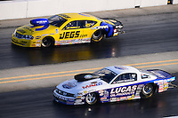 Sept. 14, 2012; Concord, NC, USA: NHRA pro stock driver Larry Morgan (near lane) races alongside Jeg Coughlin during qualifying for the O'Reilly Auto Parts Nationals at zMax Dragway. Mandatory Credit: Mark J. Rebilas-