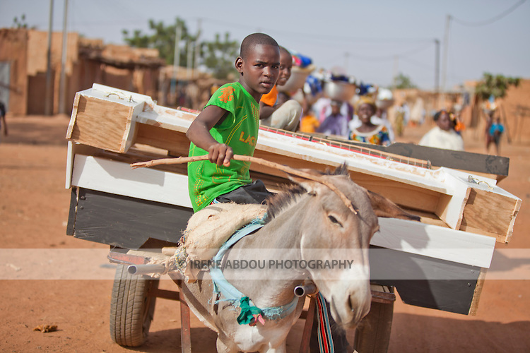In the town of Djibo in northern Burkina Faso, a Fulani wedding has taken place.  Friends and family of the bride carry gifts and possessions of the bride from the bride's home to her new home with her husband.  Leading the procession, a donkey cart transports pieces of the bride's new bed.