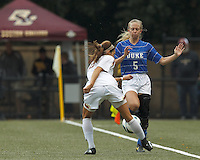 Boston College midfielder Coco Woeltz (2) centers Duke University clearing attempt as Duke University midfielder Kaitlyn Kerr (5) pressures.Boston College (white) defeated Duke University (blue/white), 4-1, at Newton Campus Field, on October 6, 2013.