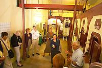 A group of visitors in the winery - concrete storage and fermentation tanks - Chateau La Grave Figeac, Saint Emilion, Bordeaux