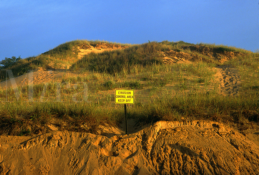 Cliff and sand dunes along the shoreline shows signs of continued erosion. Warning sign.