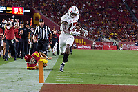 LOS ANGELES, CA - SEPTEMBER 11: Kyu Blu Kelly #17 of the Stanford Cardinal intercepts a pass and avoids a tackle by quarterback Kedon Slovis #9 of the USC Trojans and dives in for a touchdown during a game between University of Southern California and Stanford Football at Los Angeles Memorial Coliseum on September 11, 2021 in Los Angeles, California.