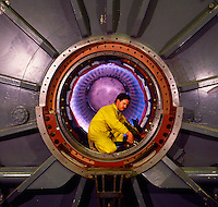 Engineer working inside very large power station generator during installation..