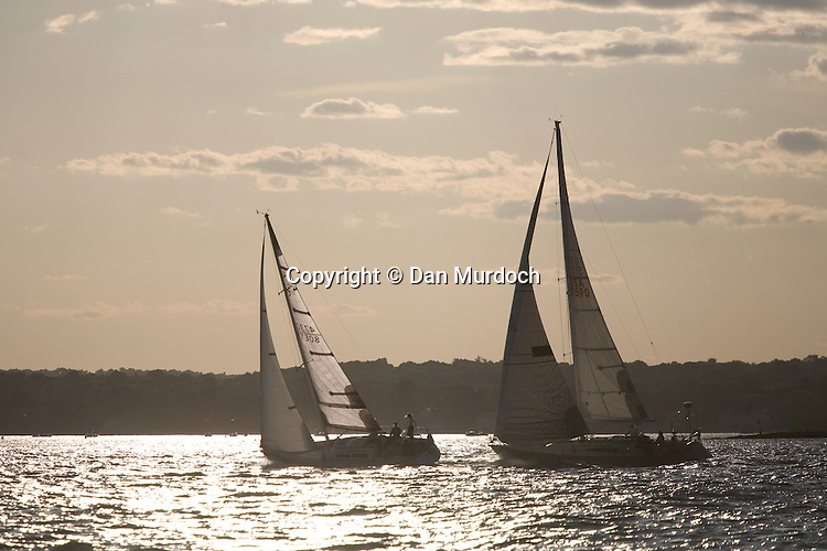 Sailboats racing in front of settng sun
