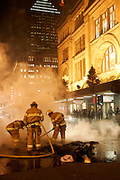 Nov 5, 2005, Montreal (QC) CANADA<br /> <br /> Montreal city firemen extinguish a sofa set abalze by protesters in downtown Montreal.<br /> Photo : (c) 2006 Pierre Roussel