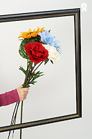 Hand of girl (6-7) holding flowers over empty picture frame (Licence this image exclusively with Getty: http://www.gettyimages.com/detail/sb10068346j-001 )